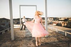 Fasonuje uroczej pięknej pary pozuje na dachu z miasta tłem Młody człowiek i zmysłowa blondynka plenerowi lifestyle zdjęcia royalty free