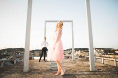 Fasonuje uroczej pięknej pary pozuje na dachu z miasta tłem Młody człowiek i zmysłowa blondynka plenerowi lifestyle zdjęcia stock