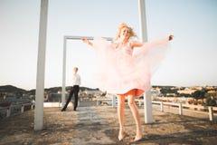 Fasonuje uroczej pięknej pary pozuje na dachu z miasta tłem Młody człowiek i zmysłowa blondynka plenerowi lifestyle fotografia royalty free