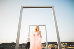 Fasonuje uroczej pięknej pary pozuje na dachu z miasta tłem Młody człowiek i zmysłowa blondynka plenerowi lifestyle obraz royalty free