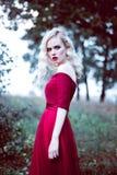 Fasonuje wspaniałej młodej blondynki kobiety w pięknej czerwieni sukni w baśniowej lasowej magicznej atmosferze Retuszujący tonow fotografia royalty free