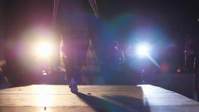 Fasonuje wybieg, model kobiety w projektantów ubrania i buty iść wzdłuż podium w spotlighting zdjęcie wideo