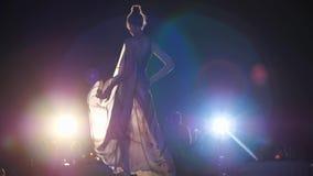 Fasonuje wybieg, wzorcowa dziewczyna w szyfon sukni i eleganccy buty iść puszka podium w jaskrawych światłach reflektorów zdjęcie wideo