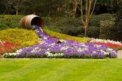 Fass mit einem Wasserfall von Blumen Stockbild