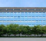 Fassade des blauen Gebäudes und eine Baumreihe vor ihm Hintergrund Stockfotografie