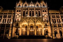 Fassade des Budapest-Parlaments nachts mit Schattenbildern von den schlendernden Touristen, Ungarn stockfoto
