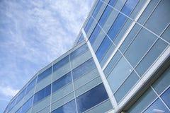 Fassade des Glases und des Stahls mit Reflexionen des blauen Himmels Stockfotografie