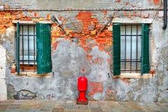 Fassade des Hauses mit Fensterläden und regged Wand in Venedig. Lizenzfreies Stockfoto