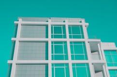 Fassade des modernen Geschäftsgebäudes mit großen widergespiegelten Fenstern und Balkon Aquamarin getont stockfotografie