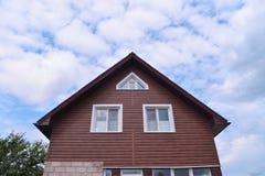 Fassade des modernen Hauses bedeckt mit Abstellgleise auf blauem Hintergrund des bewölkten Himmels Hausreparatur und -bau Stockfotos