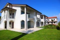 Fassade des weißen zweistöckigen Hauses mit Garten Lizenzfreie Stockfotos
