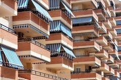 Fassade des Wohngebäudes mit Balkonen und Markisen von der Sonne Stockfotos
