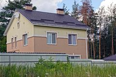 Fassade eines privaten Gebäudes mit Fenstern hinter einem braunen Zaun Lizenzfreie Stockfotos