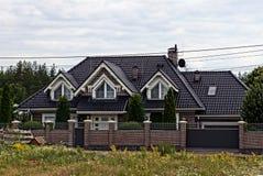 Fassade eines privaten Gebäudes mit Fenstern hinter einem braunen Zaun Stockfotografie