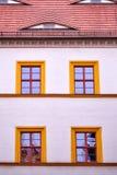 Fassade mit vier Orange gestalteten Fenstern Lizenzfreie Stockfotos