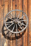 Fassade of an old, wooden Cottage with Cartwheel at Sunlight, close up Stock Photos