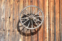 Fassade of an old, wooden Cottage with Cartwheel at Sunlight, close up Royalty Free Stock Photo