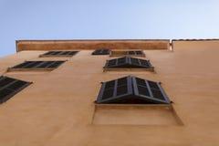 Fassade von beige spanischen Mittelmeerhäusern gegen einen klaren blauen Himmel Lizenzfreie Stockbilder