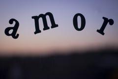 Fassen Sie amor Liebe ab, die auf spanisch in den Buchstaben mit Sonnenuntergang buchstabiert wird Stockbild