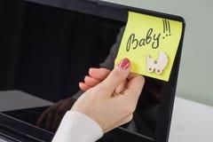 Fassen Sie Baby auf dem Papieraufkleber ab, der auf Computer fest ist Stockbild