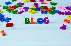 Fassen Sie Blog von den kleinen mehrfarbigen hölzernen Buchstaben auf einer weißen Brandung ab Stockfoto
