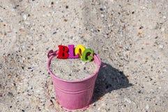 Fassen Sie Blog von hölzernen Buchstaben in einem rosa Eimer mit Sand ab Stockbild