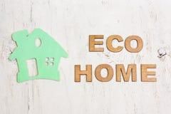 Fassen Sie das Öko-Haus ab, das von den hölzernen Buchstaben gemacht werden und ein grünes Haus auf einem whi Lizenzfreies Stockfoto