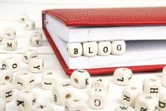 Fassen Sie das Blog ab, das in Holzklötze im roten Notizbuch auf weißes Holz geschrieben wird Stockfoto
