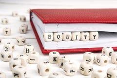 Fassen Sie das Eigenkapital ab, das in Holzklötze im Notizbuch auf weiße Tabelle geschrieben wird Stockbilder