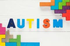 Fassen Sie den Autismus ab, der von den bunten Holzklötzen auf hölzernem Hintergrund aufgebaut wird lizenzfreie stockbilder