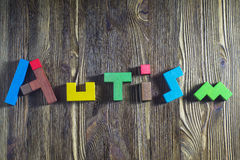 Fassen Sie den Autismus ab, der von den hölzernen Puzzlespielen auf einem hölzernen Hintergrund aufgebaut wird Lizenzfreies Stockfoto