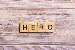 fassen Sie den Helden ab, der auf Würfel auf hölzernem Hintergrund geschrieben wird Lizenzfreie Stockfotografie