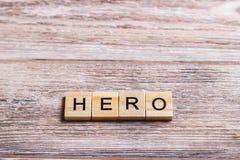 fassen Sie den Helden ab, der auf Würfel auf hölzernem Hintergrund geschrieben wird Stockfotografie