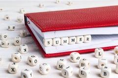 Fassen Sie den Sommer ab, der in Holzklötze im roten Notizbuch auf weißen wo geschrieben wird Lizenzfreie Stockbilder