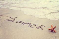 Fassen Sie den Sommer ab, der in Sand auf den Strand und die Starfish geschrieben wird Sommerferien, Ferientapete, Postkartenhint Lizenzfreies Stockfoto