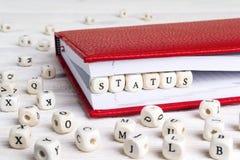Fassen Sie den Status ab, der in Holzklötze im roten Notizbuch auf weißen wo geschrieben wird Stockbild