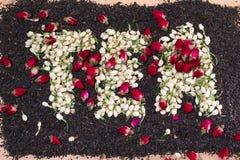 Fassen Sie den Tee ab, der von getrockneten Jasminblumenknospen über schwarzen Teeblättern mit den getrockneten zerstreuten Rotro Lizenzfreies Stockfoto