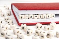 Fassen Sie den Untertitel ab, der in Holzklötze im roten Notizbuch auf Weiß geschrieben wird Lizenzfreie Stockfotografie