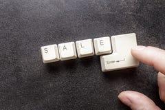 Fassen Sie den Verkauf ab, der unter Verwendung der Tasten und des Zeigefingers auf das en geschrieben wird Lizenzfreie Stockbilder