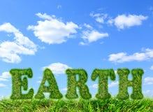 Fassen Sie die Erde ab, die vom grünen Gras auf blauem Himmel gemacht wird Stockfotografie