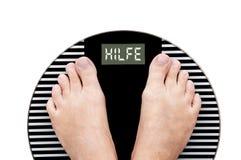 Fassen Sie die Hilfe ab, die auf Deutsch (Hilfe) geschrieben wird auf eine Gewichtsskala Lizenzfreie Stockbilder