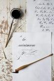 Fassen Sie die Kalligraphie ab, die auf Papier, mit Kalligraphiewerkzeugen in Hintergrund geschrieben wird Stockfotos