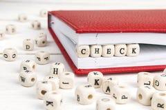 Fassen Sie die Kontrolle ab, die in Holzklötze im Notizbuch auf weißes hölzernes geschrieben wird Lizenzfreies Stockfoto