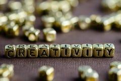 Fassen Sie die KREATIVITÄT ab, die von den kleinen goldenen Buchstaben auf der Braunrückseite gemacht wird stockfotografie