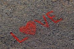 Fassen Sie die LIEBE ab, die auf den Asphalt, Boden geschrieben wird Rote Farbe der Kreide Stockfotos