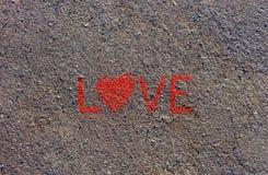 Fassen Sie die LIEBE ab, die auf den Asphalt, Boden geschrieben wird Rote Farbe der Kreide Stockbild