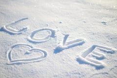Fassen Sie die Liebe ab, die auf den Schnee und das Herz geschrieben wird Lizenzfreies Stockfoto