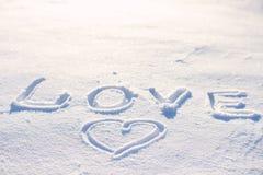 Fassen Sie die Liebe ab, die auf den Schnee und das Herz geschrieben wird Lizenzfreie Stockfotos