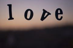 Fassen Sie die Liebe ab, die in den Buchstaben auf Fenster mit Sonnenuntergang buchstabiert wird Lizenzfreie Stockfotos