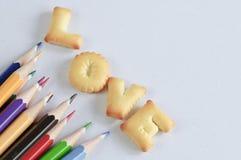 Fassen Sie die LIEBE ab, die von den Crackern und von farbigen Bleistiften gemacht wird   Stockbilder